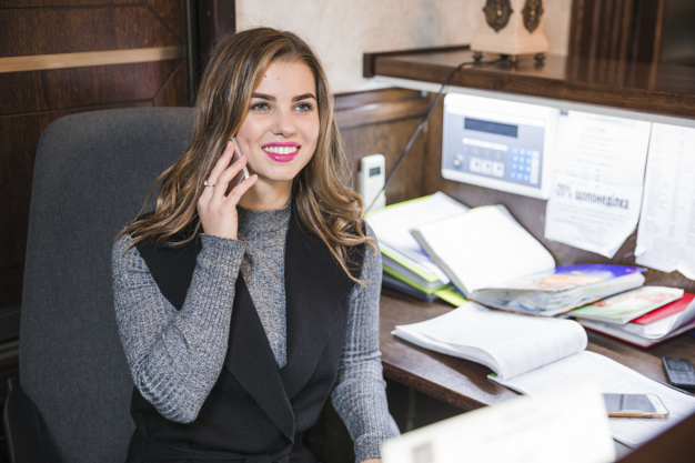 positive-confident-attractive-young-receptionist-sitting-table-talking-cell-phone_23-2148033353