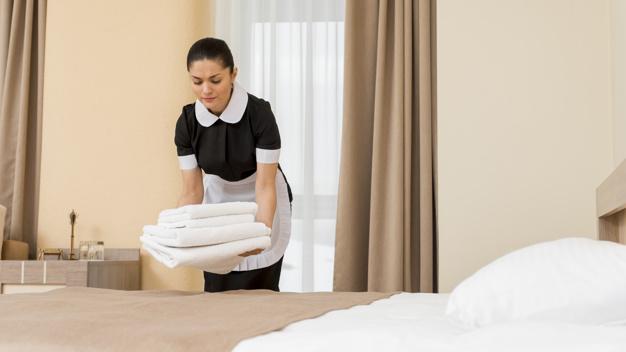 chambermaid-preparing-hotel-room_23-2148095222