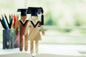 back-school-concept-two-people-sign-wood-with-graduation-celebrating-cap-open-textbook_4236-1283